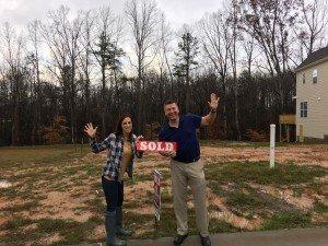 "Lynsie and Bray proudly place their ""SOLD"" sticker on the lot number sign!"