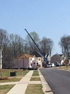 View of the crane lifting and placing trusses onto their home